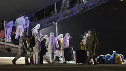Penumpang mengambil barang bawaan mereka saat turun dari pesawat kargo di Bandara Etimesgut, Ankara, Turki, Sabtu (1/2/2020). Turki memulangkan warganya dari Wuhan menyusul wabah virus corona di kota tersebut. (Photo by Adem ALTAN/AFP)