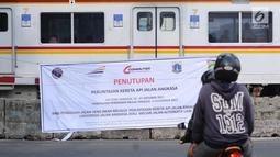 Pengendara melintas di depan spanduk sosialisasi penutupan perlintasan kereta di Jalan Angkasa, Jakarta, Minggu (15/10). Penutupan secara permanen perlintasan KA di Jalan Angkasa akan dilakukan pada 3 November mendatang. (Liputan6.com/Helmi Fithriansyah)