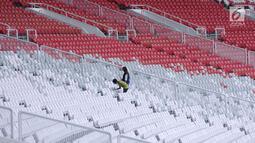 Pekerja membersihkan tempat duduk penonton di Stadion Gelora Bung Karno, Jakarta, Jumat (12/1). Rencananya, Stadion GBK akan diresmikan penggunaannya pasca renovasi oleh Presiden Joko Widodo, Minggu (14/1). (Liputan6.com/Helmi Fithriansyah)