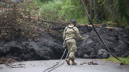 Garda Nasional Angkatan Darat AS memeriksa lahar dingin setelah letusan yang terjadi pada gunung berapi Kilauea di Hawaii (8/5). Usai letusan gunung berapi tersebut lahar dingin memenuhi jalan dan memutus lalu lintas. (Mario Tama / Getty Images / AFP)
