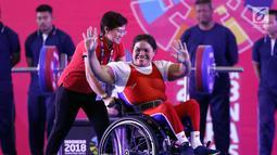Atlet Para Powerlifting Indonesia, Nurtani Purba melambaikan tangan usai mengangkat beban di kelas Womens Up 73kg Asian Para Games 2018 di Jakarta, Rabu (10/10). Nurtani Purba meraih perak dengan total angkatan 1115 kg. (Liputan6.com/Helmi Fithriansyah)