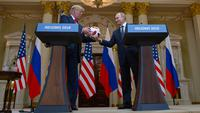 Presiden Rusia Vladimir Putin memberikan bola ke Presiden AS, Donald Trump pada konferensi pers bersama di Helsinki, Finlandia, Senin (16/7). Bola itu sebagai penghormatan karena AS akan menjadi tuan rumah Piala Dunia 2026. (AP/Pablo Martinez Monsivais)