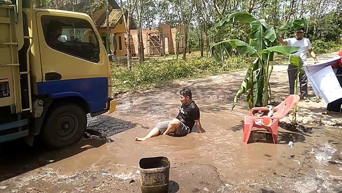 Warga Tanjung Batu Ogan Ilir menggelar teaterikal mandi air comberan di lubang jalan untuk menyindir respon lambat Pemkab Ogan Ilir (Liputan6.com / Nefri Inge)
