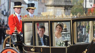 Putri Eugenie dan Jack Brooksbank menaiki kereta kencana usai melangsungkan pernikahan di Kapel St. George, Windsor Castle, London, Inggris,  Jumat (12/10). Putri Eugenie merupakan anak bungsu Pangeran Andrew dan Sarah Ferguson. (AP Photo/Rui Vieira)