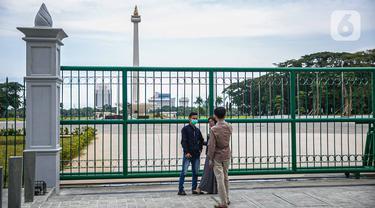 Warga berfoto di belakang Monumen Nasional atau Monas di Jakarta, Jumat (1/1/2021). Walaupun Monas ditutup warga tetap memanfaatkan libur Tahun Baru untuk berwisata dan berfoto di kawasan Monas. (Liputan6.com/Faizal Fanani)