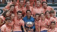 Ball girls dan ball boy melakukan foto bersama dengan Rafael Nada usai meraih trofi Prancis Terbuka 2018 di Roland Garros stadium, Paris, (10/6/2018). Nadal menang atas Dominic Thiem tiga set 6-4, 6-3, 6-2. (AP /Michel Euler)
