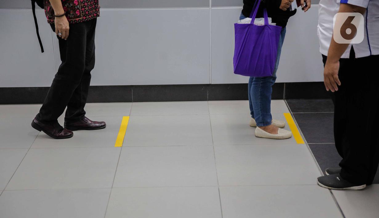 Calon penumpang mengantre di garis yang telah diberi stiker panduan jarak di stasiun MRT Bundaran HI, Jakarta, Kamis (19/3/2020). Masyarakat kini lebih waspada dalam menanggapi penyebaran virus corona Corona-19 dengan seiring bertambahnya kasus tersebut di Tanah Air. (Liputan6.com/Faizal Fanani)
