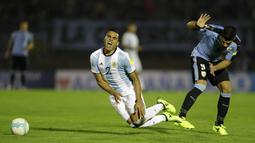 Pemain Argentina, Gabriel Mercado (kiri) menahan sakit berebut bola dengan pemain Uruguay, Luis Suarez pada laga kualifikasi Piala Dunia 2018 di Montevideo, Uruguay, (31/8/2017). Argentina bermain imbang 0-0. (AP/Natacha Pisarenko)