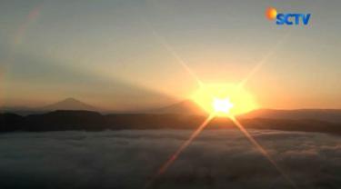 Melihat matahari terbit sambil menikmati sensasi duduk di atas awan saat berkunjung ke Bukit Brujul di Kebumen, Jawa Tengah.
