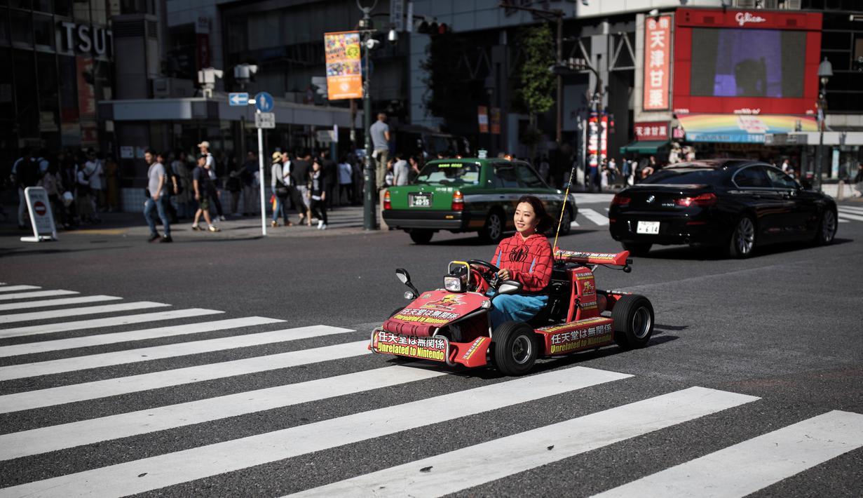 Seorang wanita mengendarai go-kart di persimpangan Shibuya di Tokyo, Jepang (23/5/2019). Shibuya adalah salah satu distrik khusus kota Tokyo, Jepang. Distrik kota ini didirikan pada 15 Maret 1947. (AFP Photo/Behrouz Mehri)