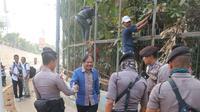Menteri Sofyan Djalil terdampak penutupan jalan di sekitar Gedung DPR, Senayan, Jakarta, Rabu (25/9/2019). Dia pun terpaksa berjalan kaki menuju ke Gedung DPR. (Radityo Priyasmoro/Liputan6.com)
