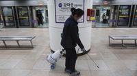 Petugas melakukan disinfeksi pada pegangan eskalator di stasiun kereta bawah tanah di Seoul, Selasa (28/1/2020). Korea Selatan telah mengonfirmasi kasus virus corona ke-4 di negaranya pada Senin (27/1/2020), setelah sebelumnya hanya 3 orang yang terinfeksi. (AP Photo/Ahn Young-joon)