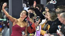 Gelandang seksi Amerika Serikat, Carli Lloyd, selfie bersama fans saat berjalan di karpet merah acara FIFA Ballon d'Or 2015 di Zurich, Swiss, Senin (11/1/2016). (AFP/Michael Bulholzer)