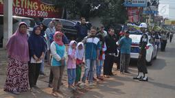 Warga sekitar Puri Cikeas bersiap menyambut iring-iringan kepergian jenazah Ani Yudhoyono menuju TMP Kalibata, Bogor, Jawa Barat, Minggu (2/6/2019). Ani Yudhoyono dimakamkan secara militer. (Liputan6.com/Immanuel Antonius)