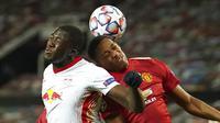 Penyerang Manchester United, Anthony Martial, duel udara dengan pemain RB Leipzig, Ibrahima Konate, pada laga Liga Champions di Stadion Old Trafford, Kamis (29/10/2020). MU menang dengan skor 5-0. (AP/Dave Thompson)