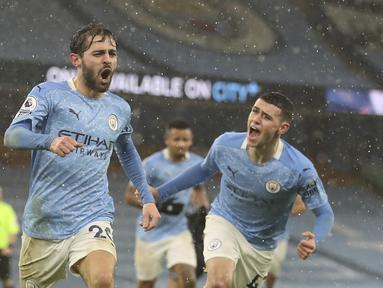 Gelandang Manchester City, Bernardo Silva melakukan selebrasi setelah mencetak gol pembuka timnya selama pertandingan lanjutan Liga Inggris di Stadion Etihad, Kamis (21/1/2021). City sukses meraih kemenangan 2-0 atas Aston Villa. (Martin Rickett / Pool via AP)