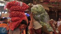 Seorang pria memanggul bawang bombay di Pasar Induk Kramat Jati, Jakarta, Selasa (22/12). Jelang Natal dan tahun baru, harga sayur mayur dan beberapa kebutuhan pokok lainnya di beberapa pasar di Jakarta merangkak naik. (Liputan6.com/Angga Yuniar)