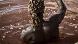 Toure, pemanen garam Gambia, melakukan manuver di samping kapalnya di Danau Retba (Danau Merah Muda) di Senegal pada 16 Maret 2021. Warna pink yang mencolok disebabkan oleh bakteri Dunaliella salina, yang tertarik dengan kadar garam yang dimiliki Retba. (MARCO LONGARI/AFP)