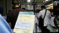 Warga membayar pajak kendaraan di Samsat Polda Metro Jaya, Jakarta, Jumat (16/11). Pemprov DKI menghapuskan sanksi administrasi Pajak Kendaraan Bermotor (PKB) dan sanksi administrasi Bea Balik Nama Kendaraan Bermotor (BBN-KB). (Liputan6.com/Johan Tallo)