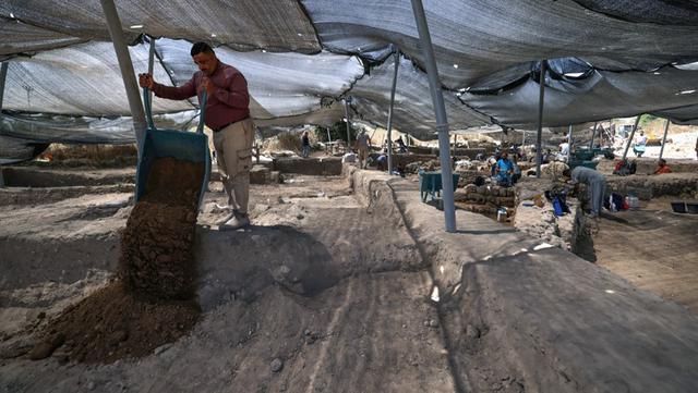 Para arkeolog dan pekerja menggali situs penggalian di mana telur ayam berusia 1.000 tahun ditemukan di Kota Yavne, Israel, Rabu (9/6/2021). Telur ayam tersebut ditemukan di tengah-tengah kotoran manusia. (Emmanuel DUNAND/AFP)