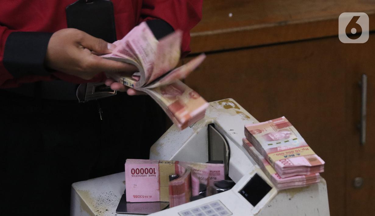Petugas menghitung uang rupiah di penukaran uang di Jakarta, Senin (9/11/2020). Nilai tukar rupiah terhadap dolar AS bergerak menguat pada perdagangan di awal pekan ini Salah satu sentimen pendorong penguatan rupiah kali ini adalah kemenangan Joe Biden atas Donald Trump. (Liputan6.com/Angga Yuniar)
