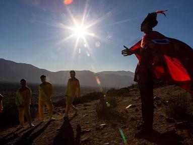 Seorang pemuda berpakaian sebagai dukun tiba untuk mengambil bagian dalam sesi foto sebelum gerhana matahari total di La Higuera, Chile (1/7/2019). Gerhana matahari total akan terjadi pada 2 dan 3 Juli di Pasifik dan Amerika Selatan. (AP Photo/Esteban Felix)
