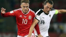 Pemain Wales, Aaron Ramsey (kiri) berebut bola dengan pemain Austria, Julian Baumgartlinger pada laga Group D kualifikasi Piala Dunia 2018 di Cardiff City Stadium, Cardiff, (2/8/2017). Wales menang 1-0. (David Davies/PA via AP)