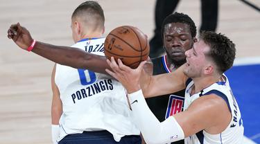 Pebasket Dallas Mavericks, Luka Doncic, berebut bola dengan pemain Los Angeles Clippers, Reggie Jackson, pada gim kedua playoff NBA 2020 di AdventHealth Arena, Kamis (20/8/2020). Maverick menang 127-114 atas LA Clipppers. (AFP/Ashley Landis-Pool/Getty Images)