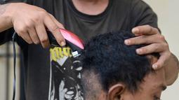 Seorang anak Punk dicukur rambutnya di Banda Aceh (9/1). Provinsi Aceh menjadi salah satu daerah di Indonesia yang menerapkan hukum Syariah bagi masyarakatnya. (AFP Photo/Chaideer Mahyuddin)