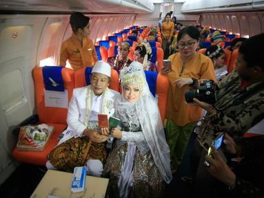 Sepasang mempelai menunjukan buku nikah usai menjalani prosesi nikah massal di kampus STTKD, Yogyakarta, Senin (4/4/2016). Sebanyak 21 pasangan pengantin mengikuti nikah bareng angkasa di atas pesawat boing. (Liputan6.com/Boy Harjanto)