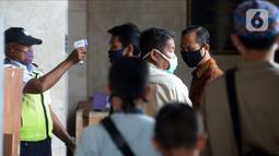 Petugas memeriksa suhu tubuh jemaah saat pelaksanaan ibadah salat Jumat di Masjid Agung At-Tin, Jakarta, Jumat (5/6/2020). Sejumlah masjid di Jakarta menggelar salat Jumat karena sudah memasuki masa PSBB transisi menuju new normal. (merdeka.com/Imam Buhori)