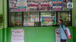 Seorang guru mendisinfeksi SDN Kenari 08, Jakarta, Selasa (6/4/2021). Skema yang akan diterapkan adalah pembelajaran tatap muka secara bergantian dengan maksimum 50 persen dari kapasitas ruangan. (Liputan6.com/Faizal Fanani)