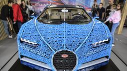 Pengunjung mengamati replika mobil Bugatti Chiron dari jutaan balok Lego Technic pada pameran di Taman Gorky Moskow, Selasa (23/7/2019). Satu juta keping LEGO ditambah bongkahan mesin yang dipasang tanpa tambahan lem, memakan waktu 13.438 jam, untuk dikembangkan dan dirakit. (Alexander NEMENOV/AFP)