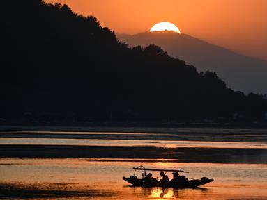Nelayan menunggu di perahu kecil setelah memancing di Danau Dal saat matahari terbenam di Srinagar (9/9/2019). Danau Dal dijuluki sebagai Jewel in the Crown of Kashmir atau Srinagar Jewel. (AFP Photo/Tauseef Mustafa)