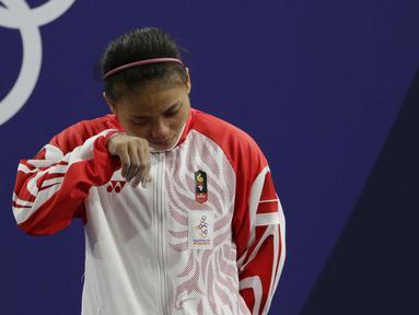 Lifter Lisa Setiawati menangis saat naik podium usai mendapatkan medali perak SEA Games 2019 cabang angkat besi nomor 45 kg di Stadion Rizal Memorial, Manila, Minggu (1/12). Dirinya meraih perak dengan total angkatan 169 kg. (Bola.com/M Iqbal Ichsan)