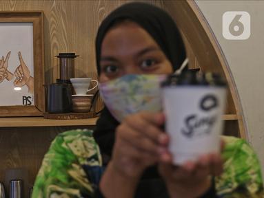Barista menunjukkan kopi buatannya di Sunyi House of Coffee and Hope, Jakarta, Jumat (15/1/2021). Rumah kopi ini mempekerjakan difabel untuk melayani pengunjung dan mengajari bahasa isyarat alfabet. (Liputan6.com/Herman Zakharia)