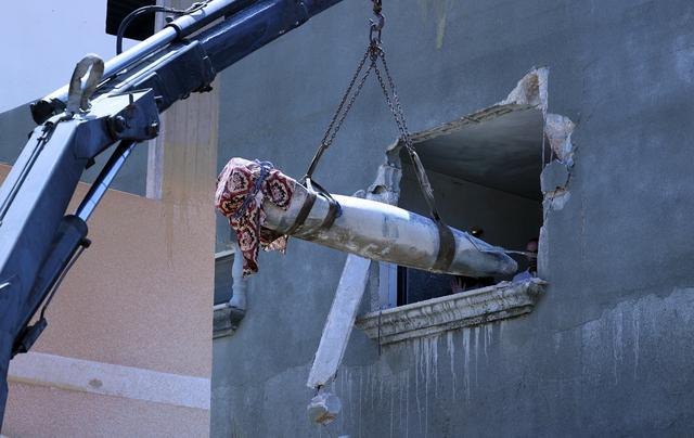 Pakar peledak Hamas mengeluarkan rudal Israel yang tidak meledak setelah menghantam di sebuah rumah di Khan Yunis, Jalur Gaza selatan (20/5/2021). Dari sekian banyak rudal Israel yang meluncur dan meledak di Gaza, ada beberapa rudal yang tak meledak usai menghantam sasaran. (AFP/Said Khatib)