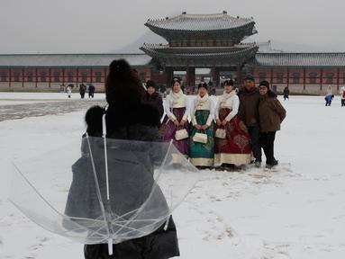 Pengunjung foto bersama saat salju turun di Istana Gyeongbok di Seoul, Korea Selatan (15/2). Istana Gyeongbok merupakan kerajaan utama selama Dinasti Joseon dan salah satu landmark terkenal di kota tersebut. (AFP Photo/Lee Jin-man)