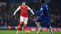 Gelandang Arsenal, Mesut Ozil, menggiring bola saat menghadapi Chelsea pada laga Premier League pekan ke-24 di Stamford Bridge, London, Rabu (22/1). Arsenal tahan imbang Chelsea 2-2. (AFP/Ben Stansall)