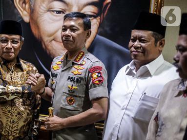 Kapolri Jenderal Pol Idham Azis menjabat tangan Ketum PBNU Said Aqil Siradj saat menyambangi Gedung PBNU di Jakarta, Selasa (12/11/2019). Kedatangan Idham merupakan tradisi pimpinan polri yang selalu menjalin silaturahmi dengan komponen masyarakat, salah satunya PBNU. (Liputan6.com/Faizal Fanani)