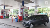 Sebuah mobil usai mengisi BBM di SPBU Jakarta, Minggu (10/2). Harga Dex diturunkan dari Rp 11.750 menjadi Rp 11.700 per liter. (Liputan6.com/AnggaYuniar)