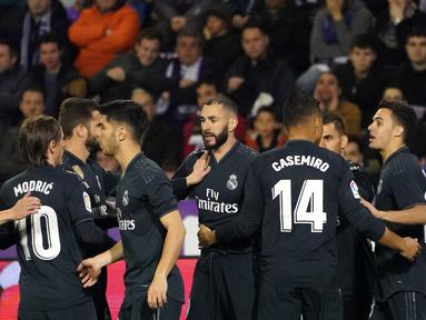 Striker Real Madrid, Karim Benzema berselebrasi usai mencetak gol ke gawang Real Valladolid selama pertandingan lanjutan La Liga Spanyol di stadion Jose Zorrilla,Valladolid (10/3). Benzema mencetak dua gol dipertanding tersebut.  (AFP Photo/Cesar Manso)