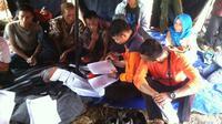 Petugas BPBD Bogor mendata korban pergerakan tanah di tenda pengungsian (Achmad Sudarno/Liputan6.com)