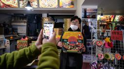 Pelanggan berpose di depan foto sutradara film Bong Joon-ho di restoran pizza bernama 'Sky Pizza' di Seoul, 13 Februari 2020. Lokasi syuting Parasite di Korea Selatan semakin ramai dikunjungi turis setelah film tersebut berhasil memboyong dan mendominasi di penghargaan Oscar 2020. (Ed JONES/AFP)