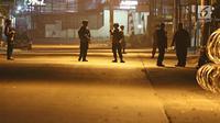 Anggota kepolisian berjaga di depan Mako Brimob Kelapa Dua pascabentrok antara petugas dengan tahanan di Depok, Kamis (10/5) dini hari. Menjelang subuh, iring-iringan kendaraan polisi masuk ke dalam area Mako Brimob. (Liputan6.com/Herman Zakharia)