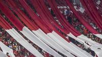 Suporter membentangkan bendera raksasa saat laga persahabatan antara Timnas Indonesia melawan Islandia di Stadion Utama Gelora Bung Karno, Jakarta, Minggu (14/1/2018). Timnas Indonesia kalah 1-4 dari Islandia. (Bola.com/M Iqbal Ichsan)