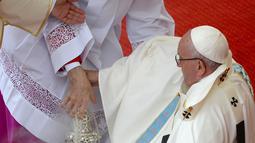 Seorang imam membantu Paus Fransiskus berdiri usai terjatuh saat berjalan menuju altar terbuka di biara Jasna Gora, Polandia, Kamis (28/7). Kunjungan Paus Fransiskus ke Polandia untuk menghadiri perayaan World Youth Day. (FILIPPO MONTEFORTE/AFP)