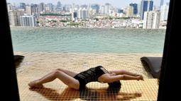 Seorang tamu berpose di kolam tanpa yang ada di hotel Dolce Hanoi Golden Lake yang baru saja diresmikan di Hanoi, Vietnam pada Kamis (2/7/2020). Hotel tersebut merupakan hotel berlapiskan emas 24 karat pertama di dunia. (Manan VATSYAYANA / AFP)