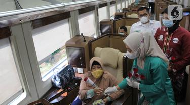 Petugas PT KAI Daop 1 Jakarta membagikan bunga kepada penumpang di Stasiun Gambir, Rabu (21/4/2021). PT KAI DAOP 1 memperingati Hari Kartini menginspirasi para penumpang agar semangat berjuang melawan pandemi COVID-19 dengan selalu menerapkan protokol kesehatan. (Liputan6.com/Herman Zakharia)