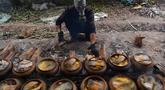 Seorang pria mengenakan masker gas saat memasak ikan di pot tanah liat menggunakan kayu bakar di provinsi Ha Nam, Vietnam, Selasa (21/1/2020). Ikan rebus adalah makanan lezat populer untuk Tahun Baru Imlek atau dikenal dengan nama Tet di utara Vietnam. (Nhac NGUYEN / AFP)